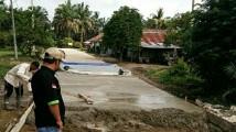 Kepala Desa Muara Bahar, Indra Guntur saat meninjau progres pembangunan jalan.