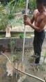 Warga sedang berupaya mengebor tanah untuk dijadikan sumur dengan peralatan sederhana.