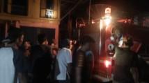 Pemadam Kebakaran dibantu warga memadamkan api.